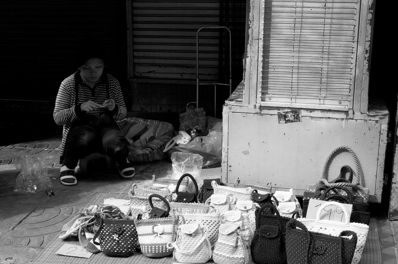 Thailänderin fertigt Taschen auf der Strasse an