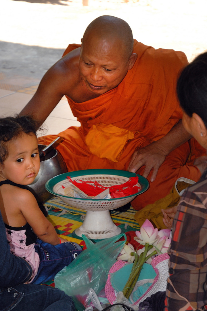 The abbot blesses the child in the temple