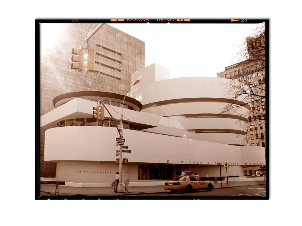The sun rises behind the Guggenheim