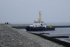 """Tonnenleger """"Lütje Hörn"""" fährt bei auflaufendem Wasser in den Hafen von Neuharlingersiel ein."""