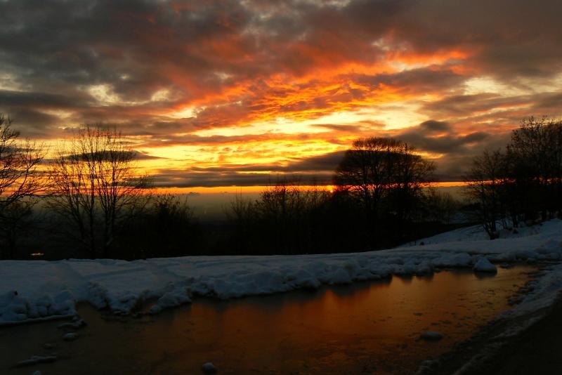 tramonto infuocato con neve e laghetto ghiacciato