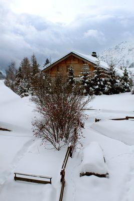 Un chalet isolé sous la neige et les nuages
