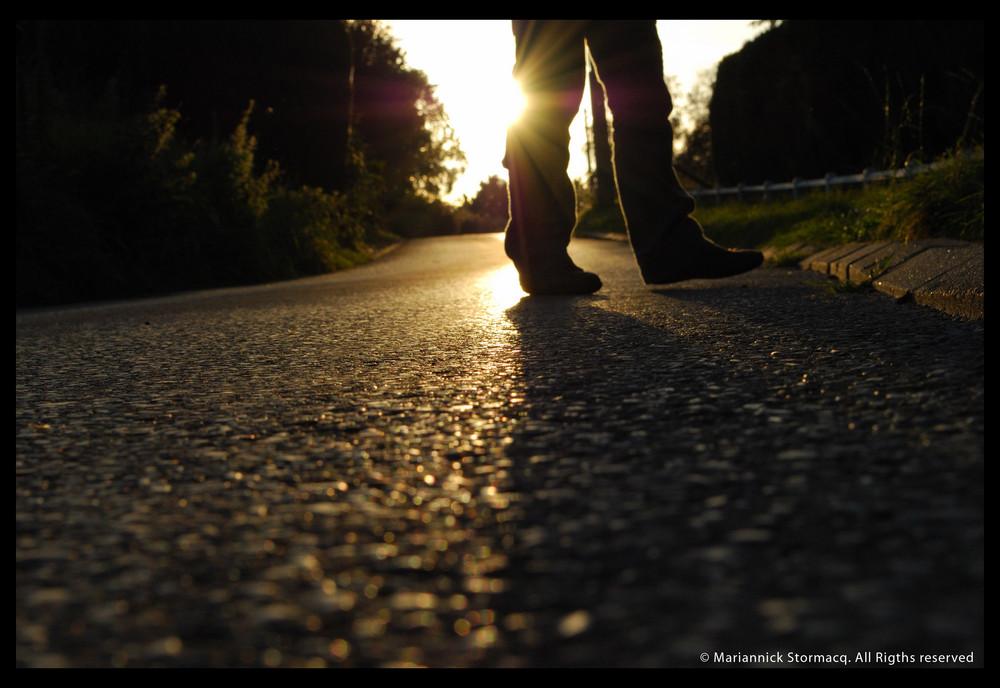 Un homme marche parmis les rayons du soleil.