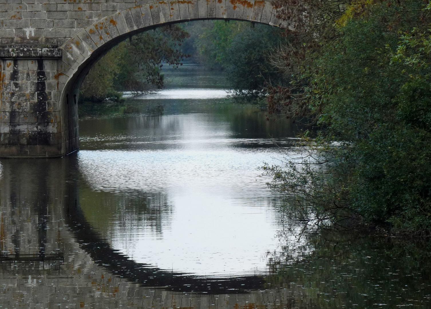 Un pont, une arche, une rivière et les reflets.