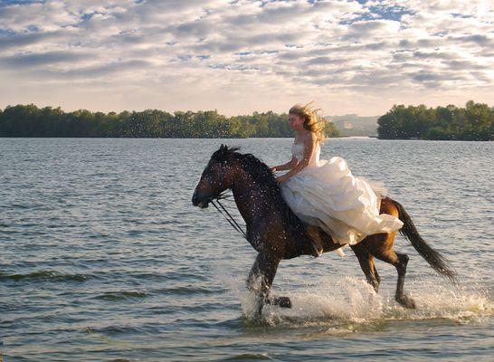 Une fille sur un cheval au galop le long du fleuve.