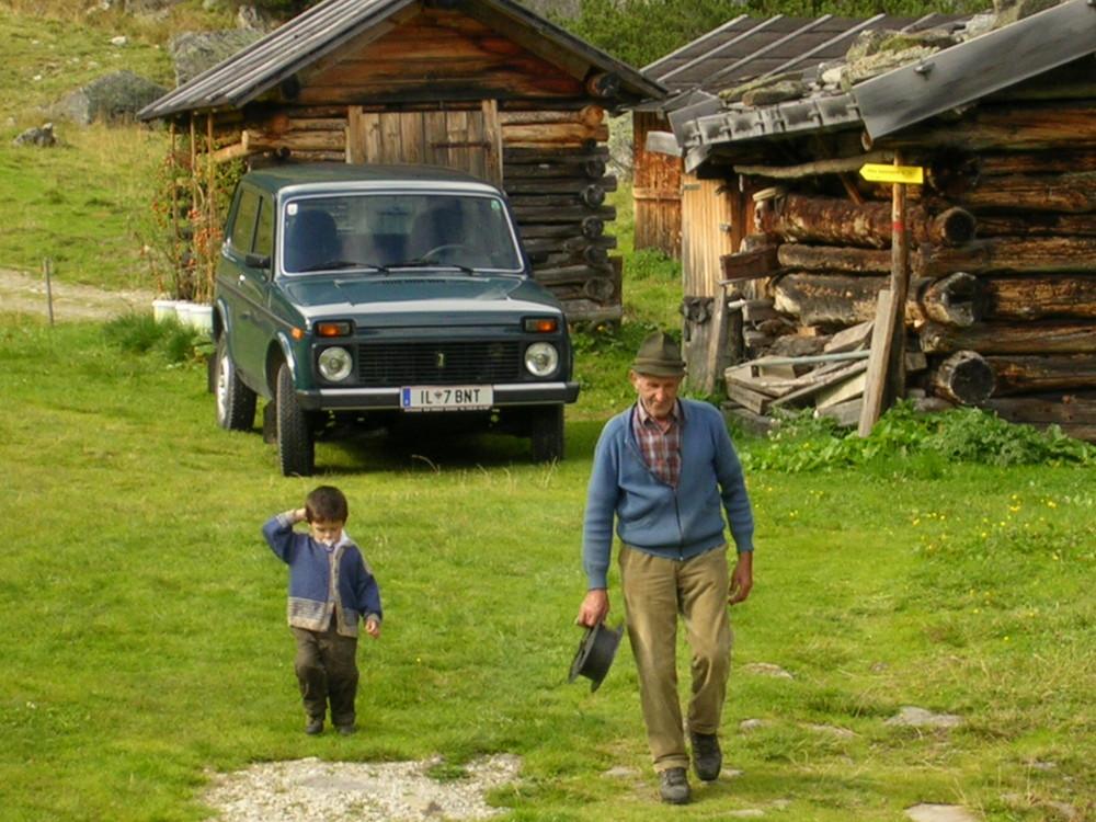 Urgrossvater und sein Enkel auf der Alm bei der Arbeit