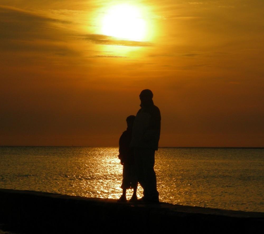 Vater und Sohn vorm Sonnenuntergang.