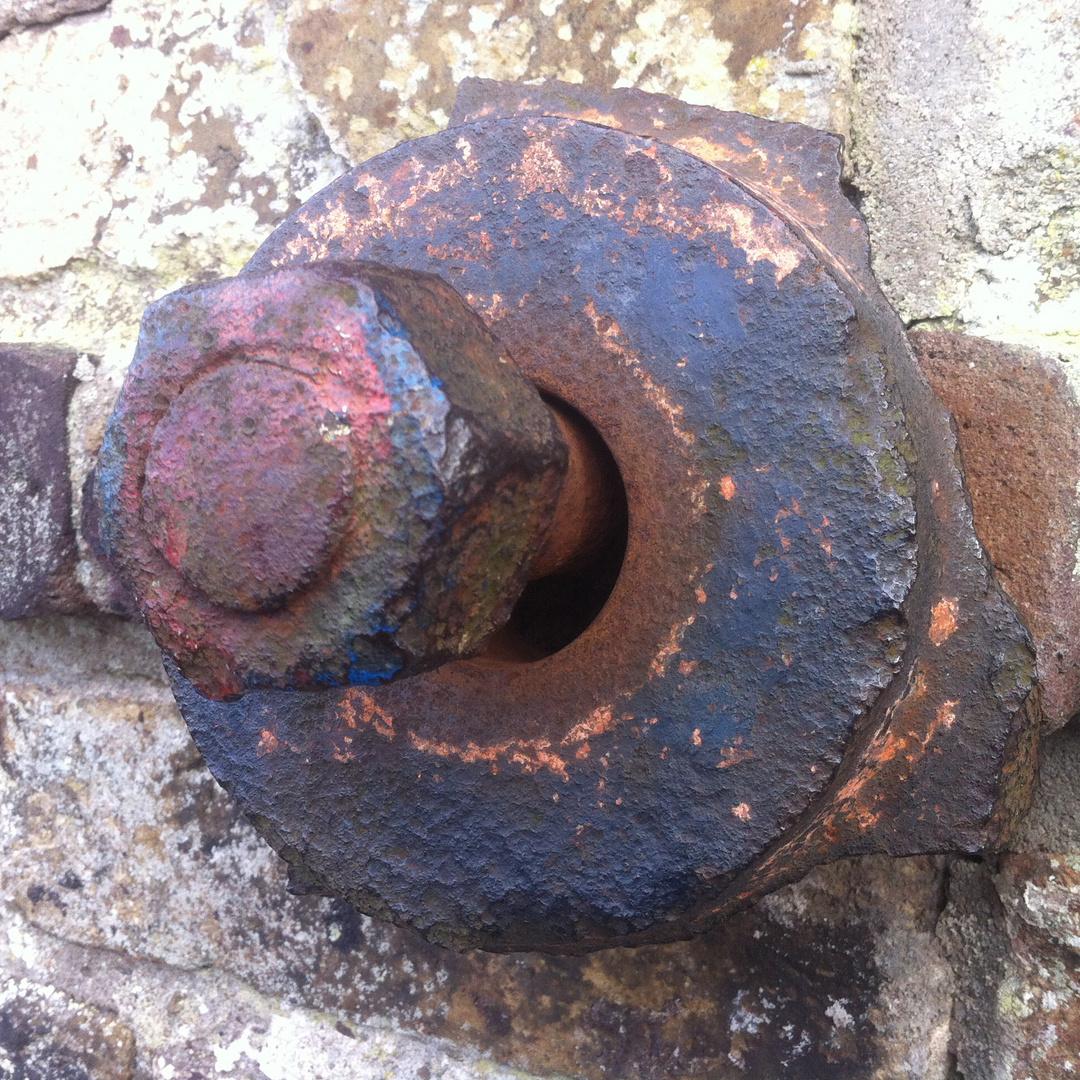 Verrostete Schraube an der Ufermauer