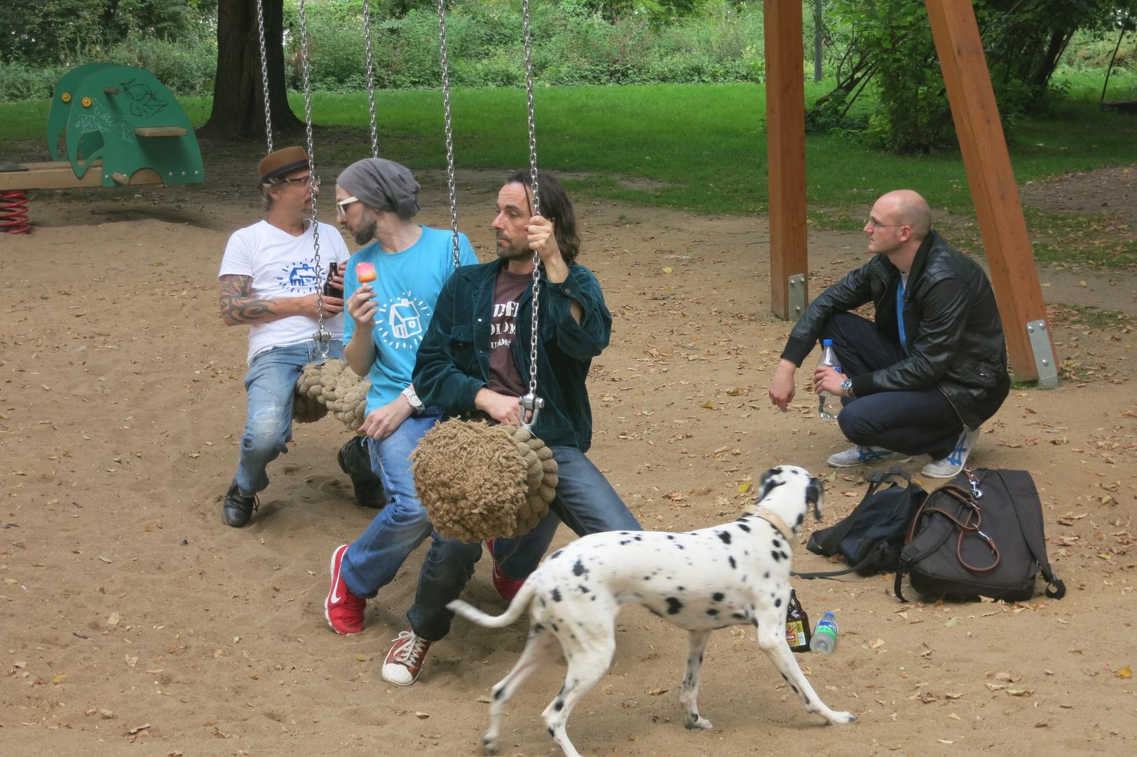 Vier Männer auf der Schaukel mit Hund