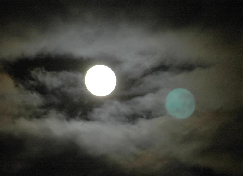 Vollmond mit Spiegelbild in einer Wolkenlücke