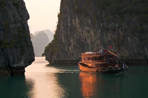 Von der Abendsonne angestrahltes Boot in der Ha Long Bucht