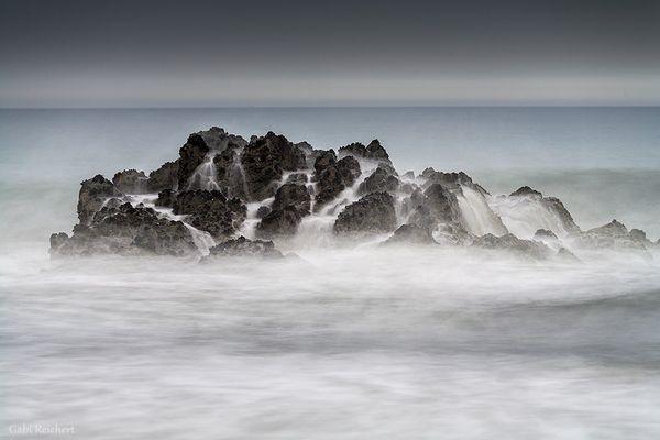 Wellen und Felsen in Regenwetter