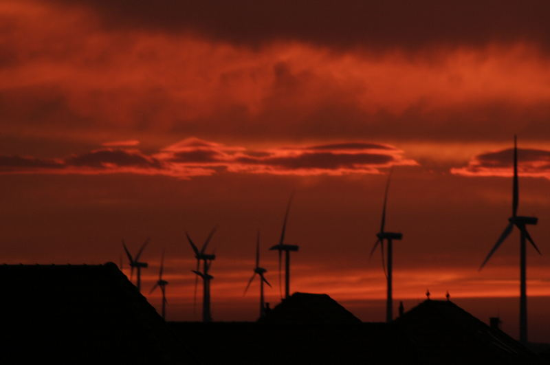 Windmills projecting against a bloodred sky