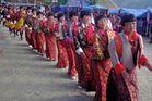 Women in traditional kira enter the tsechu