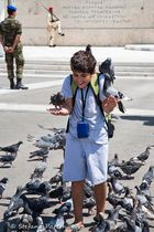 Young boy feading pigeons. Parliament and Monument of the Unknown Soldier, Athens Greece