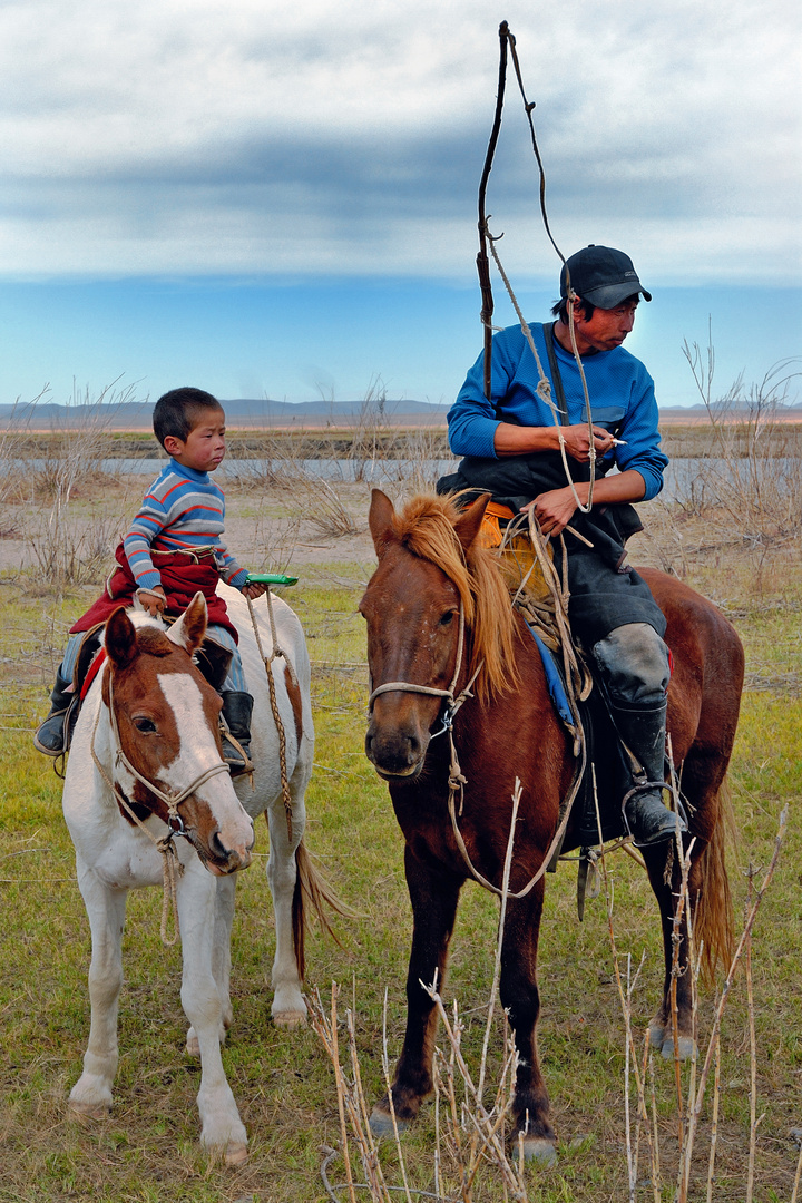 Young boy learns riding the horse