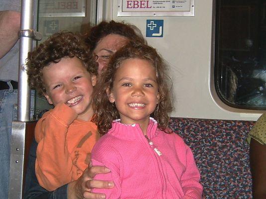 Zwei Kinder haben eine Menge Spaß auf dem Schoß ihrer noch jungen Oma (in einer U-Bahn in Berlin)