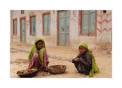 2 Mädchen beim Sammeln von Kuhdung