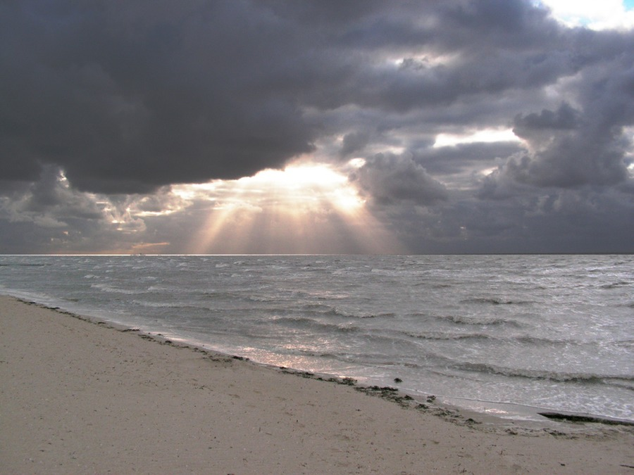 Agressive See & Sonnenloch in den Wolken