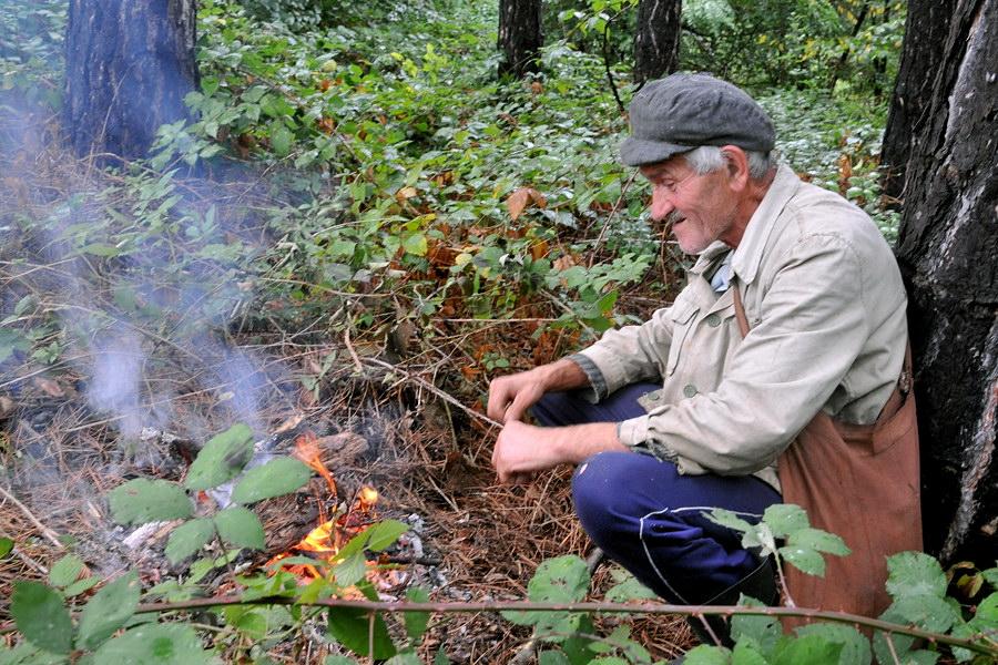 Allein im Wald, im Regen, ein Hirte wärmt sich am Feuer