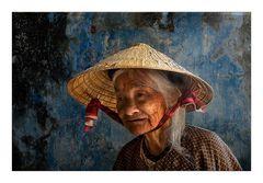 Alte Frau vor blauer Wand