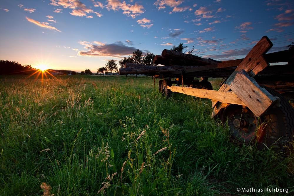 Alter Holzhänger zum Sonnenuntergang