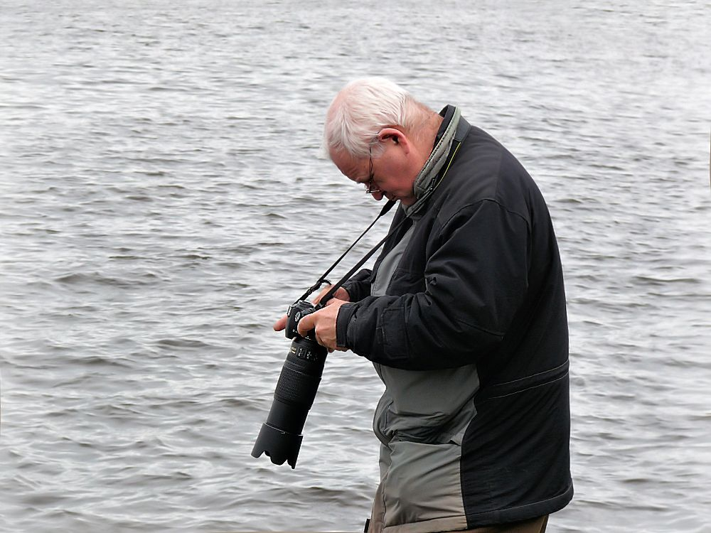 Amateur photographer adjusts his camera