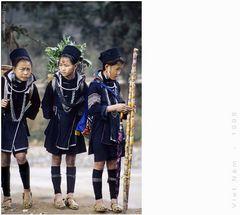 angeschnittenes Mädchen mit leerem Korb in angestrengt blickender Begleitung
