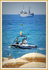 Azurblaues Meer, himmelblauer Himmel, sonnengelbe Sonnenschirme und angenehmes Wetter..