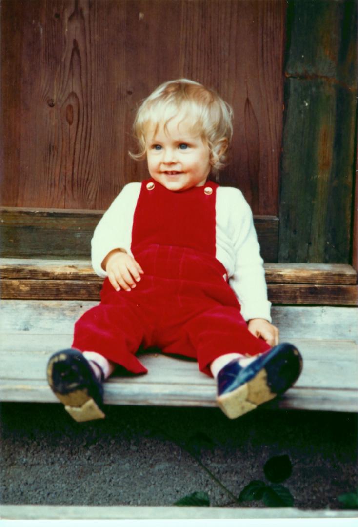 Baby sitzt vor einer Hütte