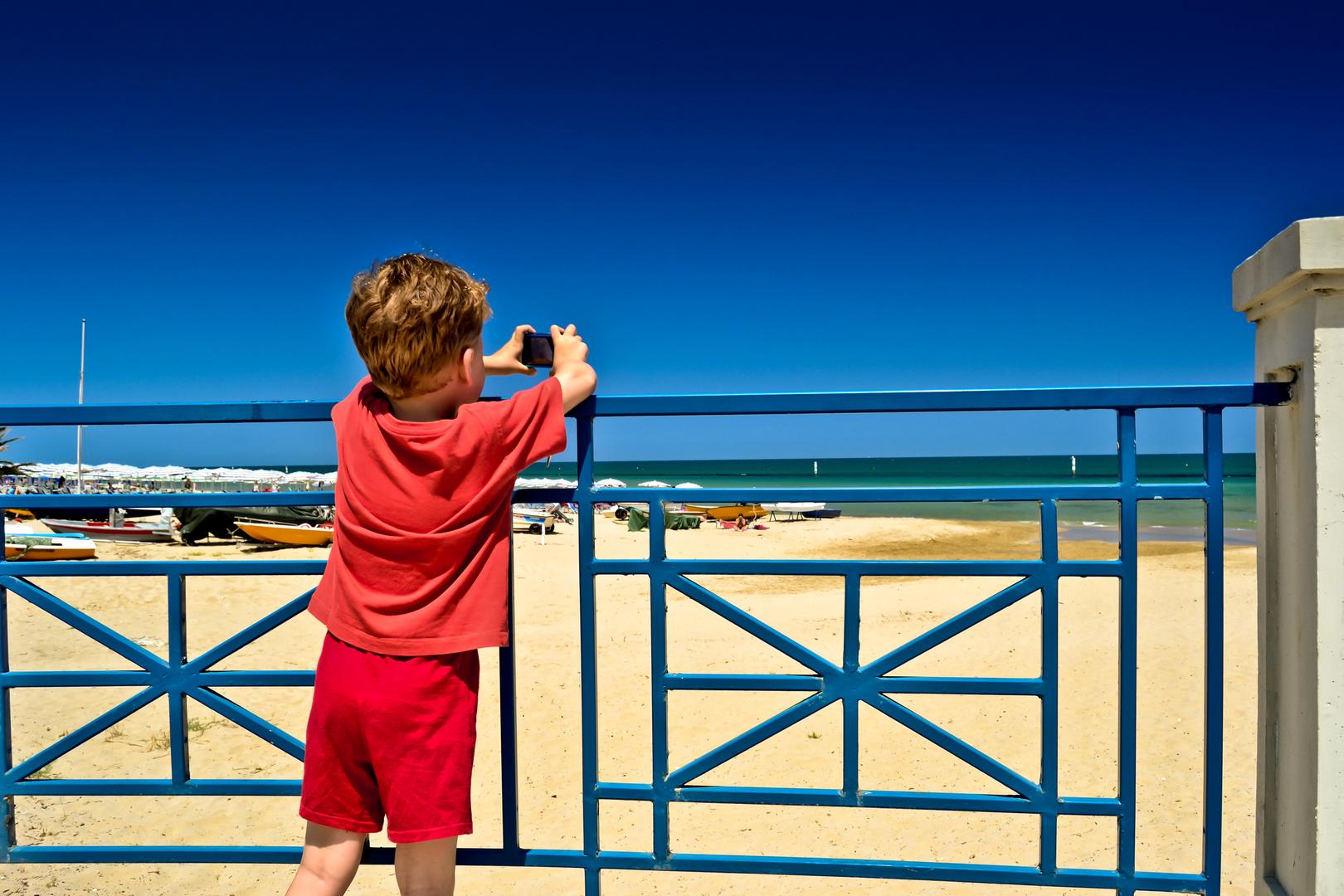 Bambino che fotografa il mare