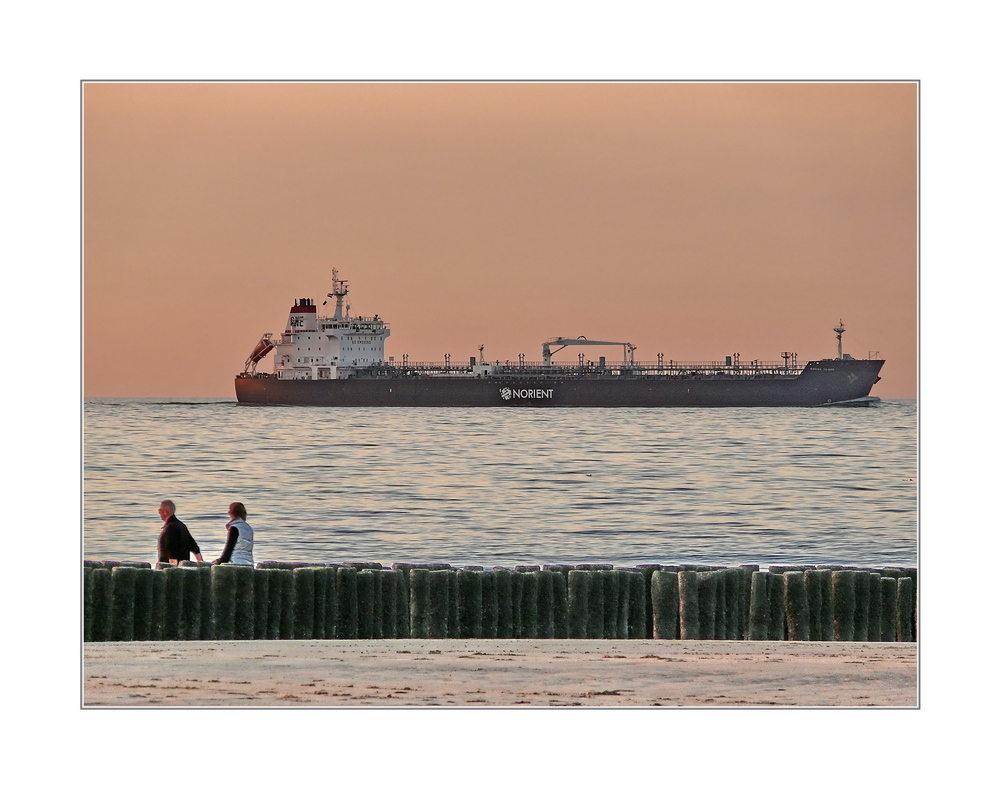 Beach walkers and tanker at sunset (the Idylic Nordsea)