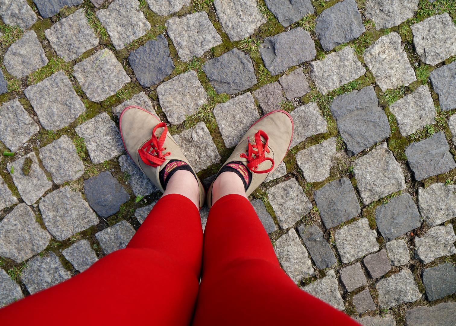 Beine eines Teenagers mit roter Strumpfhose