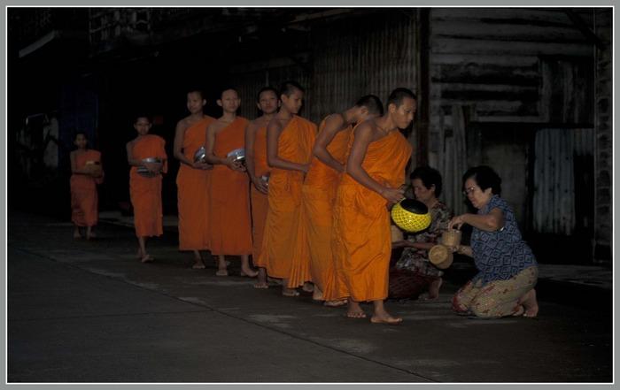 Bettelgang der Mönche kurz vor Sonnenaufgang in Chiang Khan (Nordthailand).