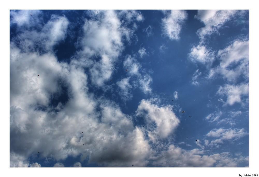 Blau-Weißer Himmel mit bunten Schirmen