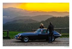 Blue E-Type in front of a red sky
