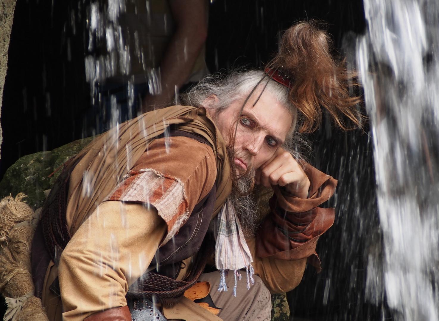 Boze man onder waterval