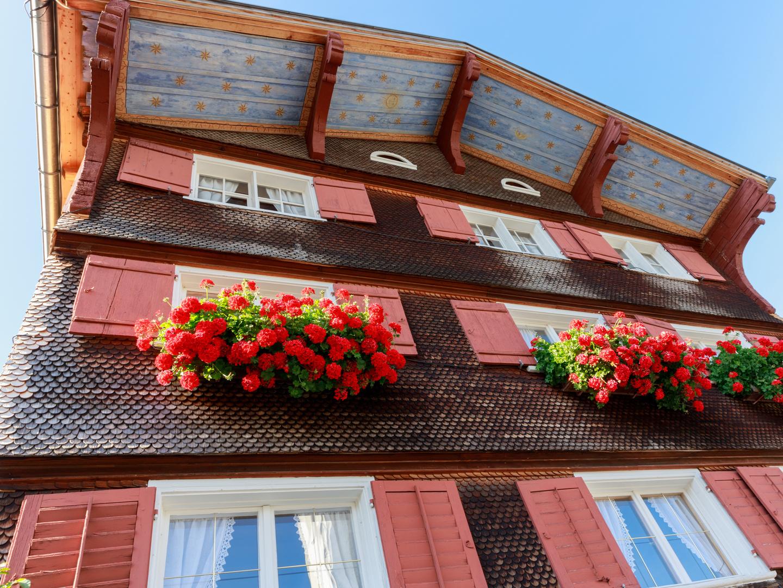 Bunte Holzfassade mit Blumenschmuck