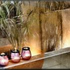 Candele e acqua in cascata in vetrina di parrucchiere.