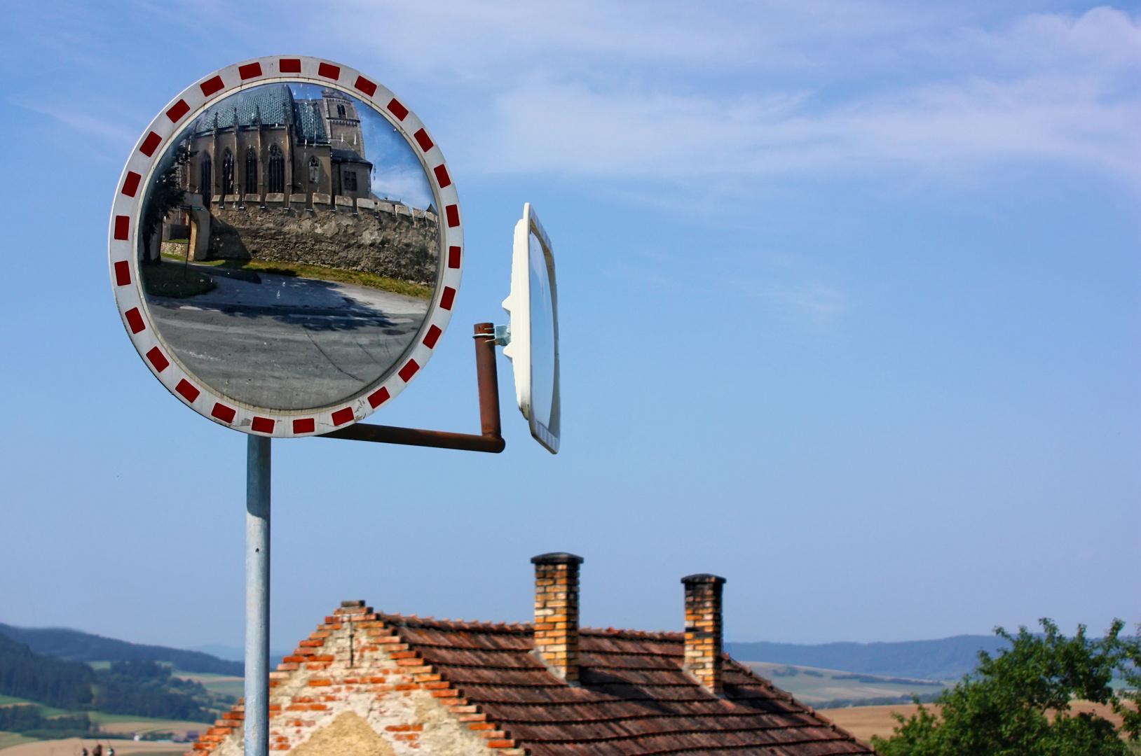 Church reflected in traffic mirror