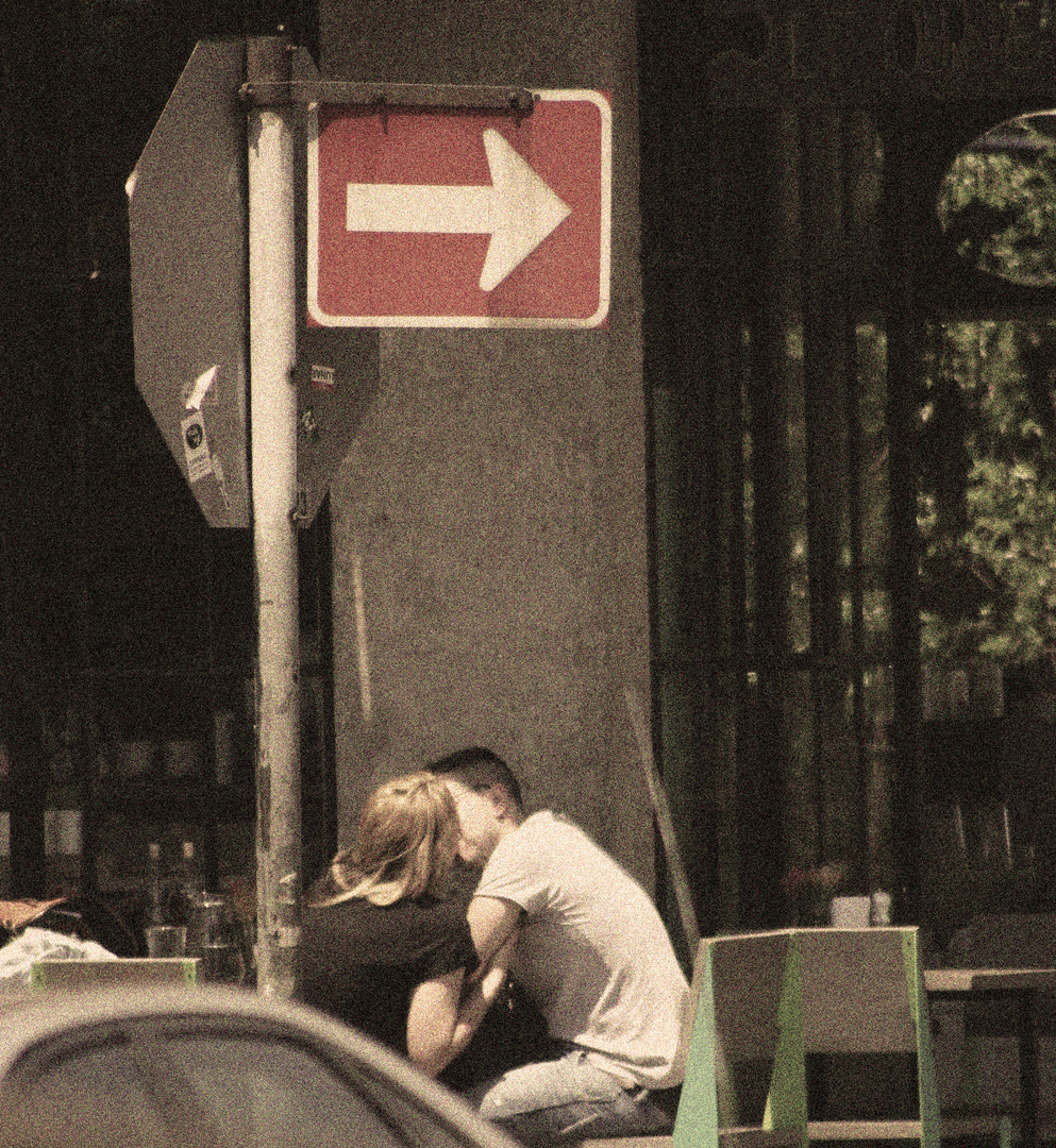 Couple Kissing At Street Cafe