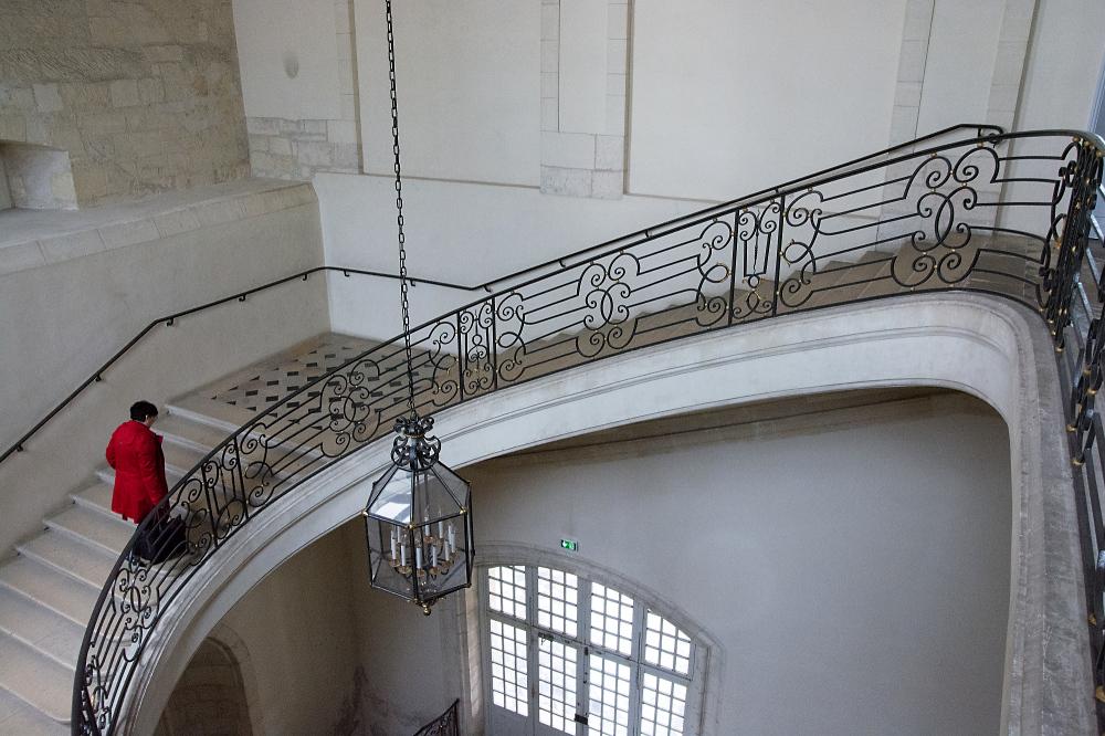 Dame in rot, eine Treppe hinaufsteigend