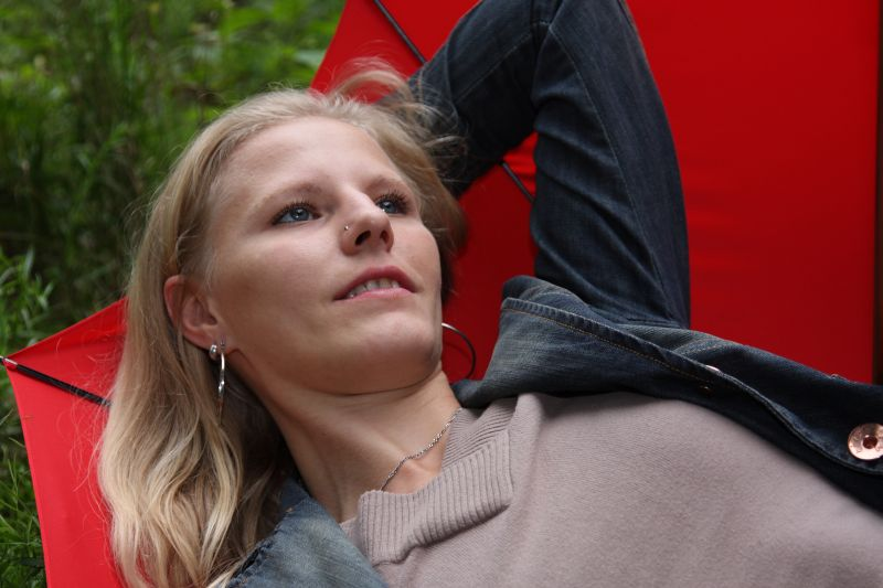 Daniela verträumt im roten Regenschirm