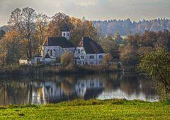 Das Pfarrhaus zwischen Kirche und See.