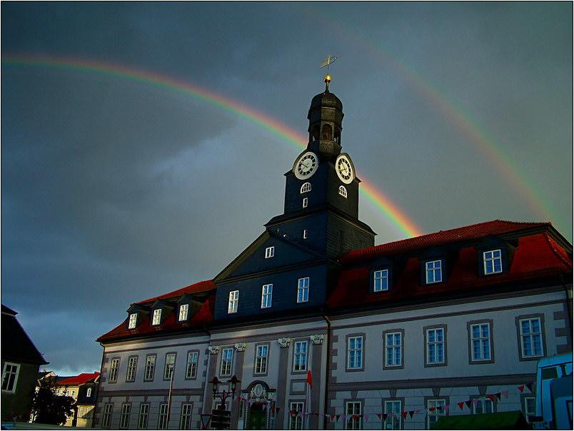 Das Rathaus in Königsee mit doppeltem Regenbogen.