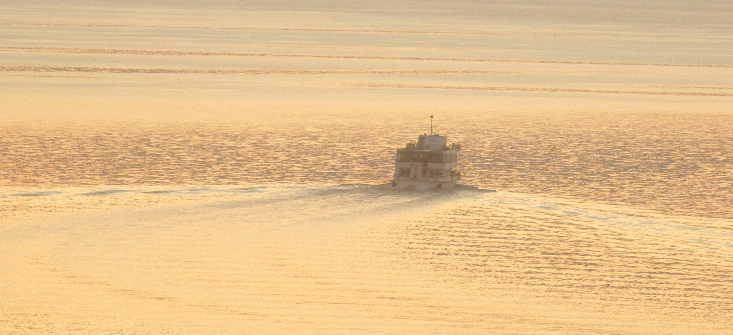 das Schiff auf dem See von der untergehenden Sonne durchflutet