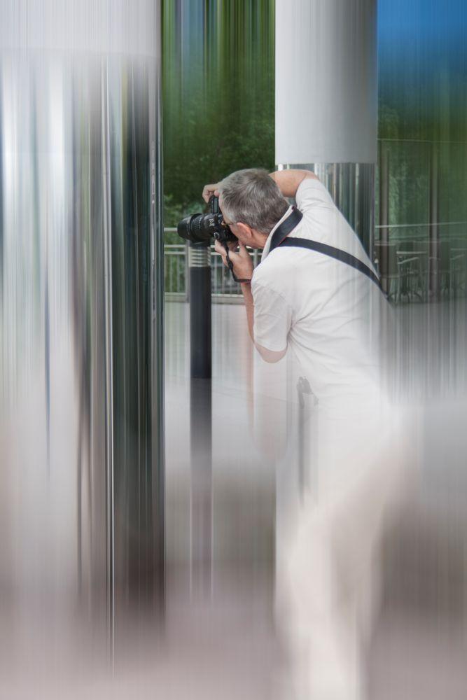 Der Fotograf fotografiert sich im Spiegel der Säule selbst