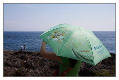 der grüne Schirm am blauen Meer
