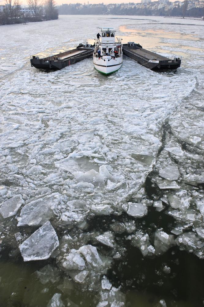 """Der Hilfseisbrecher """"REIHER"""" schiebt Eisschollen über das Wehr in Koblenz"""