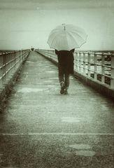 Die Frau mit dem Regenschirm, geht über die Brücke der Erinnerungen